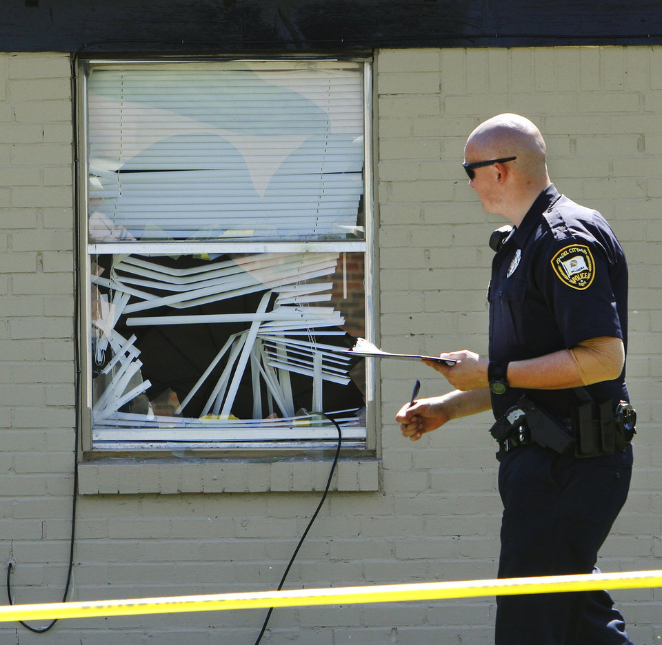 A Del City police officer takes notes while processing the crime scene on Karen Street. This window in the front of the house was broken when police tossed a phone into the house. The phone cable can be seen dangling from the window. Del City police successfully rescued a small girl from inside a house at 1920 Karen Street Wednesday morning, July 18, 2012. The child was held hostage by a man who refused to come out. He was found dead inside after the girl was removed.  Photo by Jim Beckel, The Oklahoman.