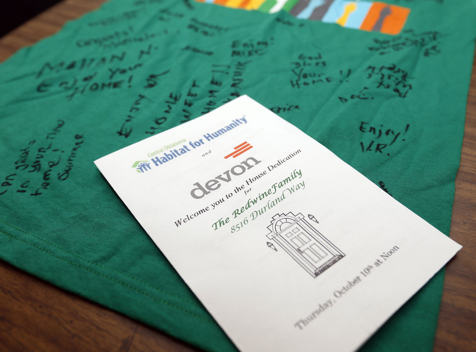 Photo - Mementos from the family's experience with Central Oklahoma Habitat for Humanity include a  program from the house dedication and a T-shirt signed by volunteers who worked on framing day.  NATE BILLINGS - The Oklahoman