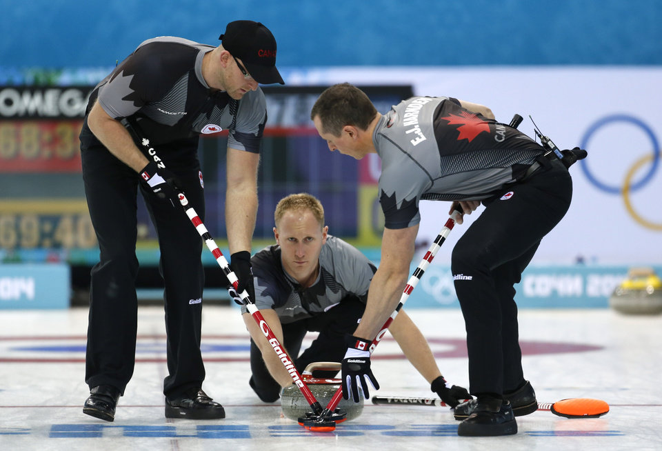 Photo - Canada's skip Brad Jacobs, center, delivers the rock to his sweepers Brian Harndin, left, and E. J. Harnden during men's curling competition against Sweden the 2014 Winter Olympics, Tuesday, Feb. 11, 2014, in Sochi, Russia. (AP Photo/Robert F. Bukaty)