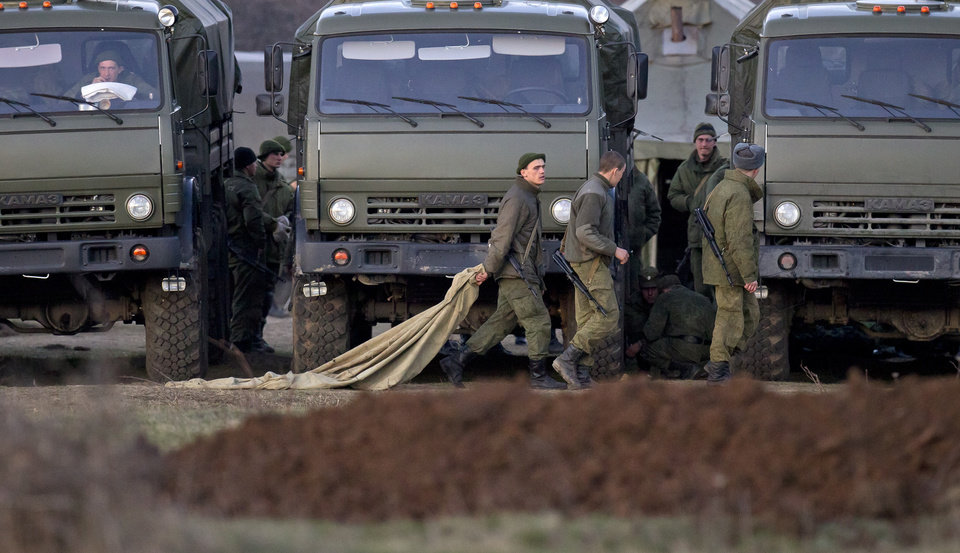Photo - Pro-Russian soldiers walk past trucks that define the limits of their staging area in the vicinity of a Ukrainian military base in Perevalne, Ukraine, Saturday, March 15, 2014. Tensions are high in the Black Sea peninsula of Crimea, where a referendum is to be held Sunday on whether to split off from Ukraine and seek annexation by Russia. (AP Photo/Vadim Ghirda)