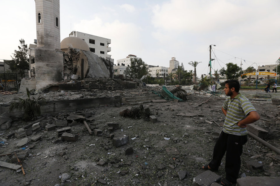 Photo - A Palestinian man inspects the Al Aqsa Martyrs mosque destroyed by an overnight Israeli strike, in Gaza City, Tuesday, July 22, 2014. Israel bombed five mosques, a sports stadium and the home of the late Hamas military chief across the Gaza Strip early on Tuesday, a Gaza police official said, as the U.N. chief Ban Ki-moon and the U.S. Secretary of State John Kerry launched a high-level effort to end two weeks of deadly fighting. (AP Photo/Lefteris Pitarakis)