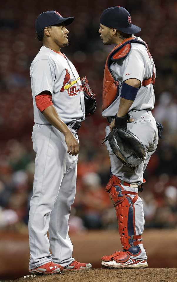 Photo - St. Louis Cardinals relief pitcher Carlos Martinez, left, talks with catcher Yadier Molina in the eighth inning of a baseball game against the Cincinnati Reds, Thursday, April 3, 2014, in Cincinnati. Martinez was the losing pitcher as Cincinnati won 1-0. (AP Photo/Al Behrman)