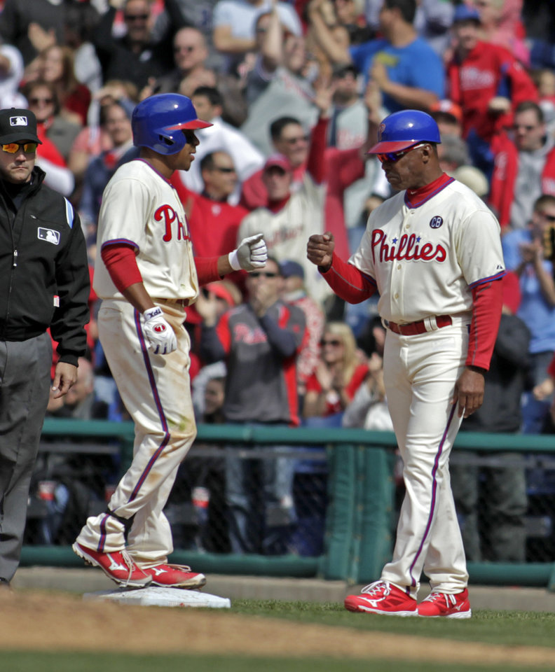 Photo - Philadelphia Phillies' Ben Revere, front left, celebrates with first base coach Juan Samuel after hitting a one-run single against the Atlanta Braves in the eighth inning of a baseball game on Thursday, April 17, 2014, in Philadelphia. The Phillies won 1-0. (AP Photo/H. Rumph Jr.)