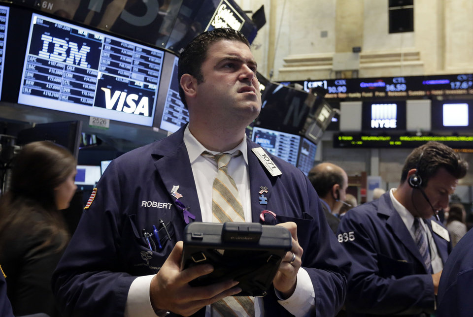 Photo - Trader Robert McQuade works on the floor of the New York Stock Exchange Wednesday, July 9, 2014.  Stocks inched higher in early trading Wednesday, reversing a two-day decline, as the quarterly earnings season got underway with some positive news from the giant aluminum company Alcoa. (AP Photo/Richard Drew)