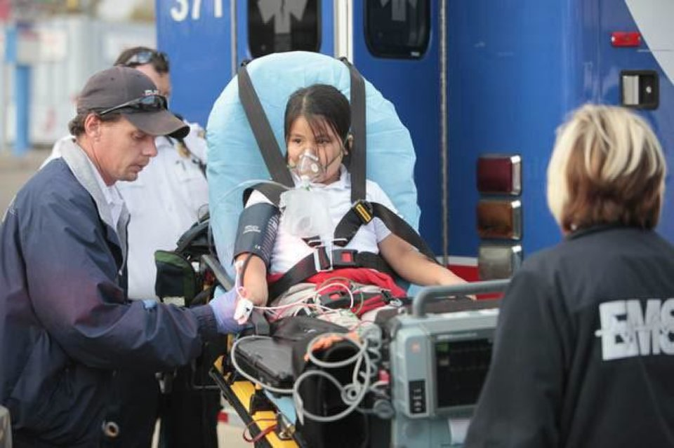 Photo - A student is loaded into an ambulance Monday to be treated for carbon monoxide poisoning at Lee Elementary School in Oklahoma City. Photo by David McDaniel, The Oklahoman