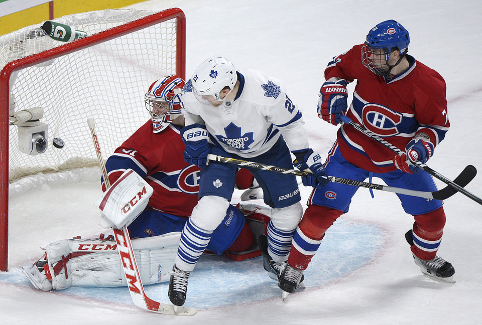 Montreal Canadiens goaltender Carey Price, left, is scored on by Toronto Maple Leafs' Phil Kessel, not seen, as Maple Leafs' James van Riemsdyk (21) and Canadiens' Alexei Emelin, right, look for a rebound during the second period of an NHL hockey game in Montreal, Saturday, Feb. 9, 2013. (AP Photo/The Canadian Press, Graham Hughes)