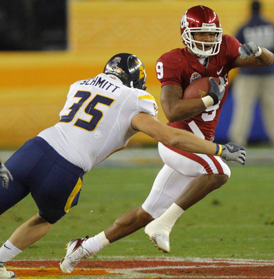 Photo - Oklahoma's Juaquin Iglesias (9) tries to get past West Virginia's Owen Schmitt (35) on a kick return during the first half of the Fiesta Bowl college football game between the University of Oklahoma Sooners (OU) and the West Virginia University Mountaineers (WVU) at The University of Phoenix Stadium on Wednesday, Jan. 2, 2008, in Glendale, Ariz. 
