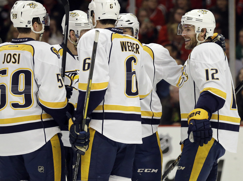 Photo - Nashville Predators' Mike Fisher (12), right, celebrates with teammates after scoring a goal during the first period of an NHL hockey game against the Chicago Blackhawks in Chicago, Friday, March 14, 2014. (AP Photo/Nam Y. Huh)