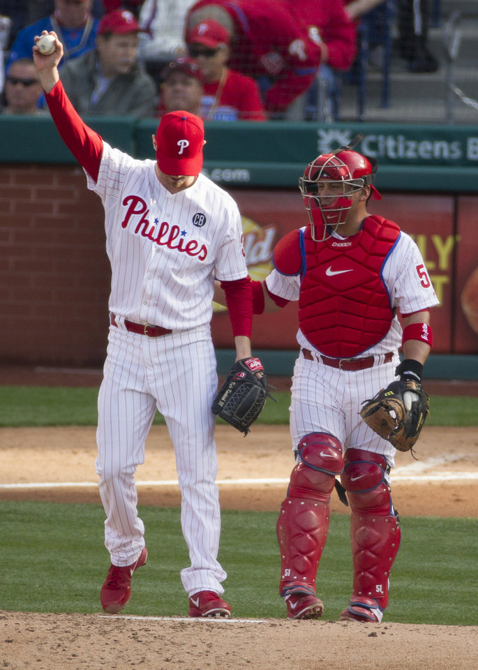 Photo - Philadelphia Phillies' starting pitcher Kyle Kendrick, left, stretches his arm as he talks with Carlos Ruiz, right, during the third inning of an MLB National League baseball game against the Milwaukee Brewers, Tuesday, April 8, 2014, in Philadelphia. (AP Photo/Chris Szagola)