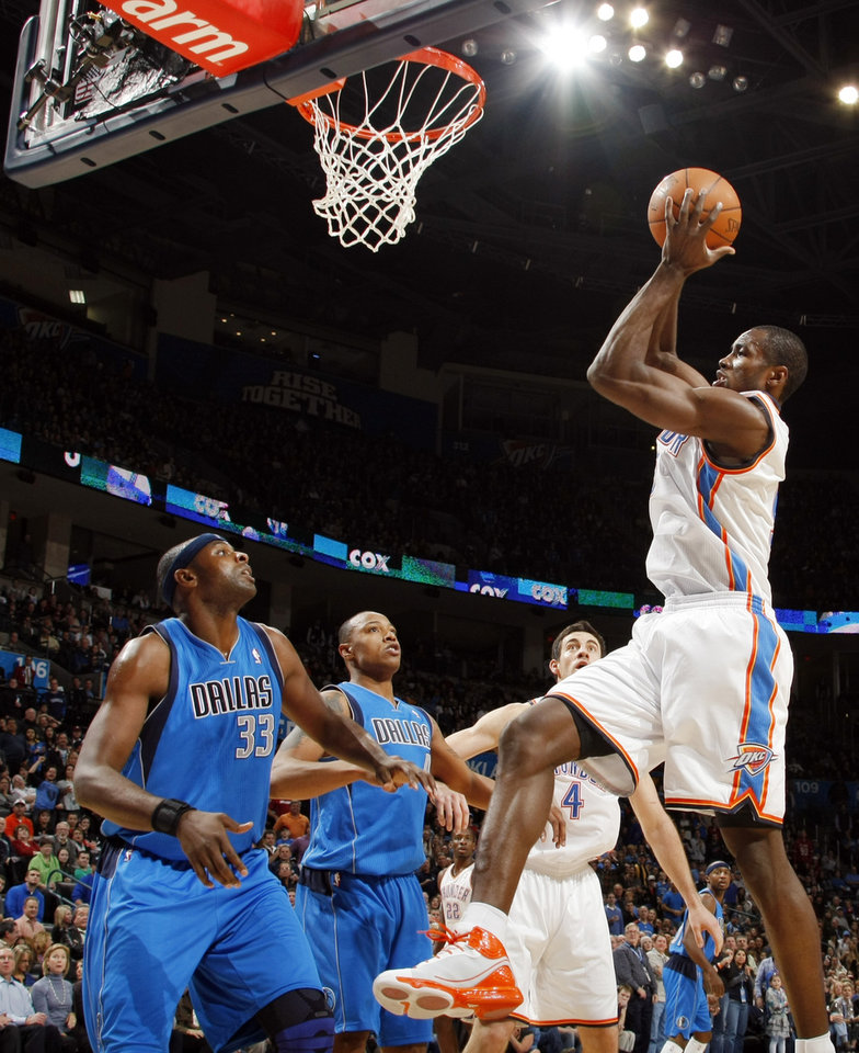 Photo - Oklahoma City's Serge Ibaka (9) looks to score in front of Brendan Haywood (33) and Caron Butler (4) of Dallas next to Oklahoma City's Nick Collison (4) during the NBA basketball game between the Dallas Mavericks and the Oklahoma City Thunder at the Oklahoma City Arena in Oklahoma City, Monday, Dec. 27, 2010. Photo by Nate Billings, The Oklahoman