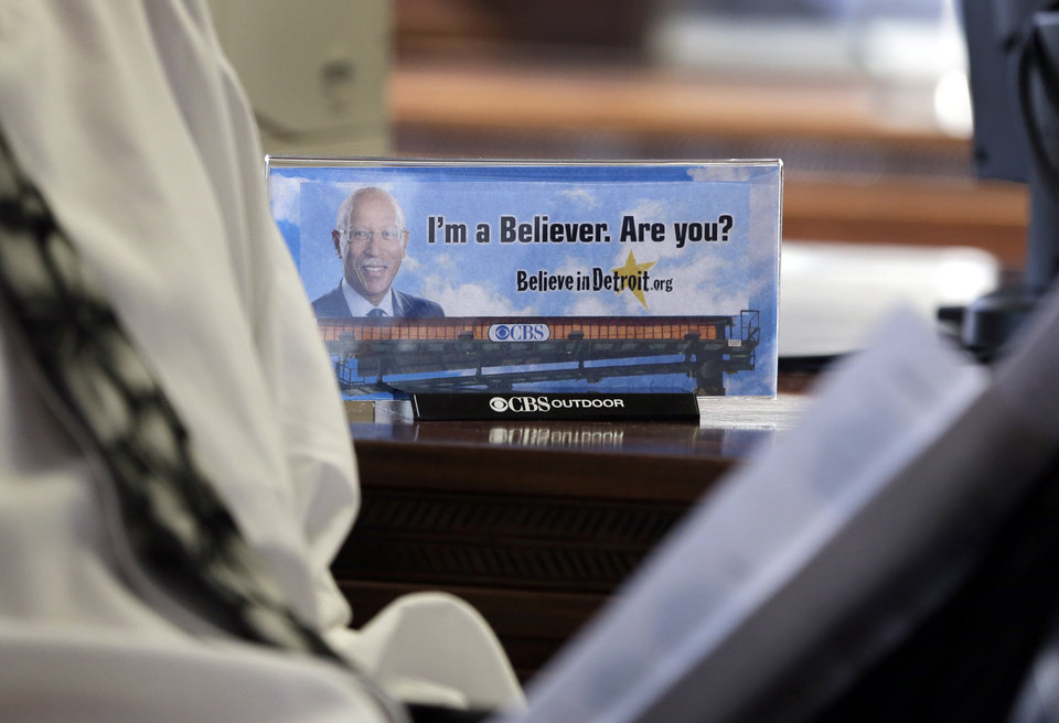 "A photograph of a billboard is seen on Detroit Mayor Dave Bing's desk during his interview with the Associated Press, Wednesday, March 6, 2013. The mayor says he believes Michigan Gov. Rick Snyder will appoint an emergency manager over the city's finances and that he ""intends to work collaboratively"" with that person. Bing says he's considering whether to appeal a determination by a state-appointed review team and Snyder that Detroit has not put forward a plan to resolve the city's serious financial problem. (AP Photo/Carlos Osorio)"