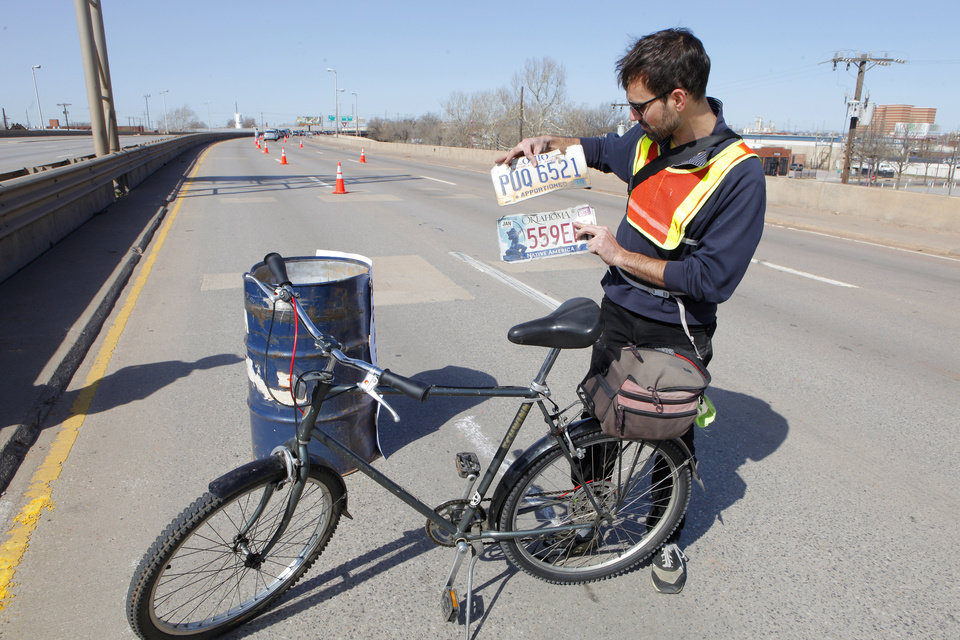 Andrew Ciscel, from Knoxville, Tenn., with two licence plates he found while bicycling on the old I-40 Crosstown in Oklahoma City Wednesday, Feb. 29, 2012. The Oklahoma Department of Transportation let folks park and walk a section of the old highway in downtown Oklahoma City. Photo by Paul B. Southerland, The Oklahoman