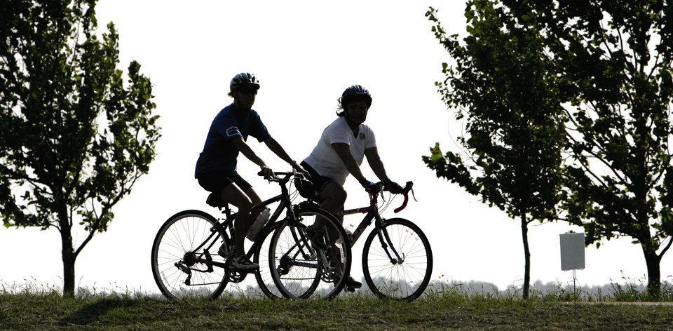 Photo -  Peggy Leonard, left, of Chickasha, Okla., and Lolli Shotts, right, of Oklahoma City, are shown in shilouette against the morning skies over Lake Overholer as they participated in the 1st Annual Tour de Cure, a fundraiser for the American Diabetes Association, which included four distances for those entered; 9 mile ride, 26 mile ride, 52 mile ride and a 100K ride ( about 62 miles), around the Lake Overholsier, Oklahoma City and Yukon areas, Saturday, June 23, 2007. By Bill Waugh, The Oklahoman.