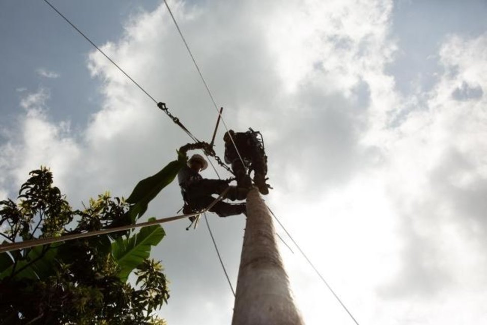 Photo -  Members of a volunteer team from electric cooperatives in Oklahoma and Colorado attach electric line to a pole as part of a project where they helped villagers bring power to a school, churches and homes in Sillab, Guatemala.