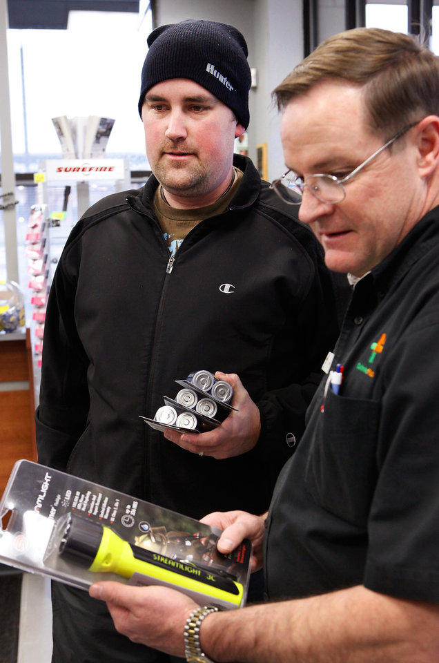 Photo - Jerry Haley, right, assists customer Jason Austin  who came into BatteriesPlus at NW 63 and May to purchase flashlight and 'D' cell batteries, Thursday,  Jan. 28, 2010. Photo by Jim Beckel, The Oklahoman