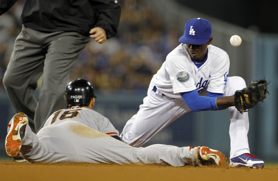 Photo -   Los Angeles Dodgers shortstop Dee Gordon can't get the handle on the ball as San Francisco Giants' Angel Pagan takes second base in the fifth inning of a baseball game in Los Angeles Monday, May 7, 2012. Gordon had two errors on the play. (AP Photo/Reed Saxon)