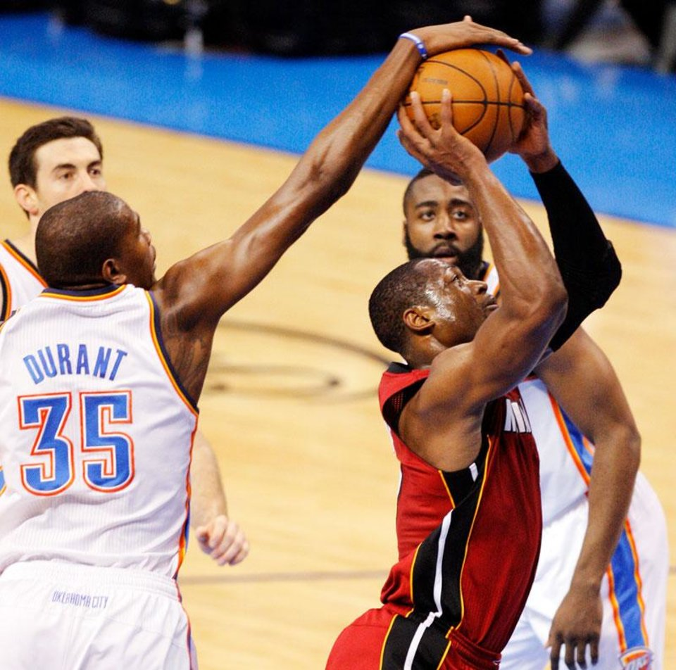 Oklahoma City's Kevin Durant (35) defends a shot by Miami's Dwyane Wade (3) as Oklahoma City's James Harden (13) and Nick Collison (4) look on during Game 1 of the NBA Finals between the Oklahoma City Thunder and the Miami Heat at Chesapeake Energy Arena in Oklahoma City, Tuesday, June 12, 2012. Photo by Nate Billings, The Oklahoman