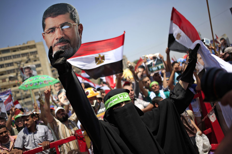 Photo - A supporter of Egypt's ousted President Mohammed Morsi wearing a head band with Arabic writing that reads,
