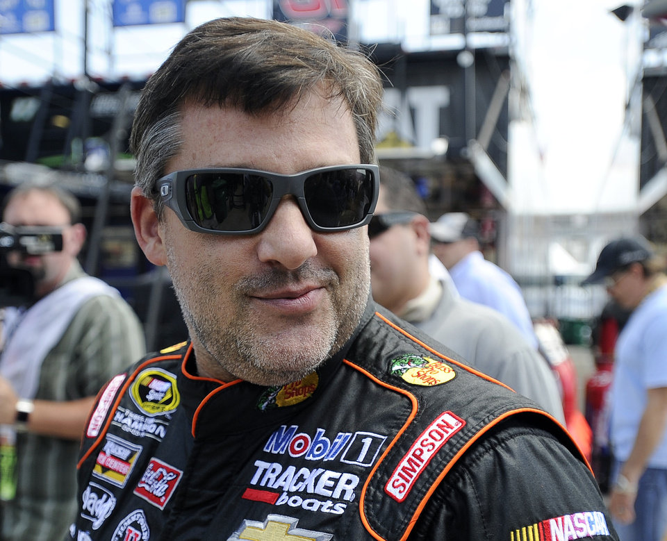 Photo - NASCAR driver Tony Stewart makes his way to his car before practicing for Sunday's auto race at Atlanta Motor Speedway in Hampton, Ga., Friday, Aug. 29, 2014. Sunday's race will be his first since his car struck and killed a fellow driver during a sprint race in New York three weeks ago. (AP Photo/John Bazemore)