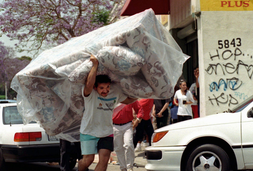 Photo -   FILE - In this April 30, 1992 file photo, a man removes a couch from a store in South-Central Los Angeles as looting and rioting continued throughout the area. The acquittal of four police officers in the videotaped beating of Rodney King sparked rioting that spread across the city and into neighboring suburbs. Cars were demolished and homes and businesses were burned. Before order was restored, 55 people were dead, 2,300 injured and more than 1,500 buildings were damaged or destroyed.( (AP Photo/Nick Ut, File)