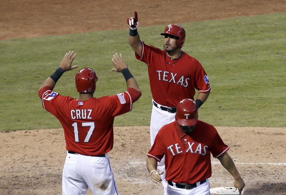 Photo - Texas Rangers' Geovany Soto, top, is greeted at the plate by Nelson Cruz (17) after hitting a three-run home run that scored Cruz and Lance Berkman, bottom, in the sixth inning of a baseball game against the Houston Astros Saturday, July 6, 2013, in Arlington, Texas. The shot came off a pitch from Astros relief pitcher Wesley Wright. (AP Photo/Tony Gutierrez)
