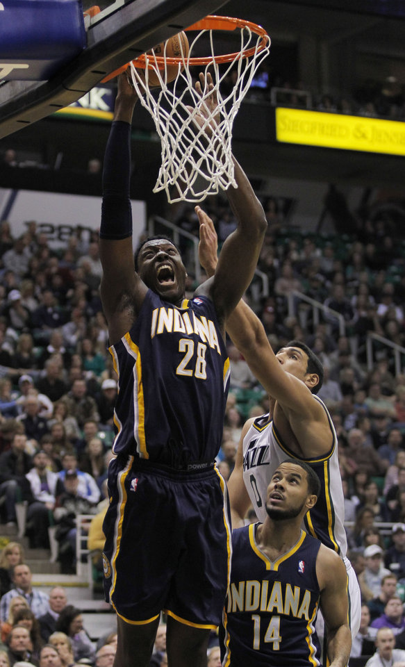 Photo - Indiana Pacers center Ian Mahinmi (28), of France, takes a layup to the hoop past Utah Jazz center Enes Kanter (0) in the first half during an NBA basketball game on Saturday, Jan. 26, 2013, in Salt Lake City. Pacers guard D.J. Augustin (14) looks on during the play. (AP Photo/Steve C. Wilson)
