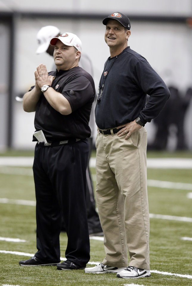 San Francisco 49ers head coach Jim Harbaugh, right, talks with offensive coordinator Greg Roman during practice on Friday, Feb. 1, 2013, in New Orleans. The 49ers are scheduled to play the Baltimore Ravens in the NFL Super Bowl XLVII football game on Feb. 3. (AP Photo/Mark Humphrey)