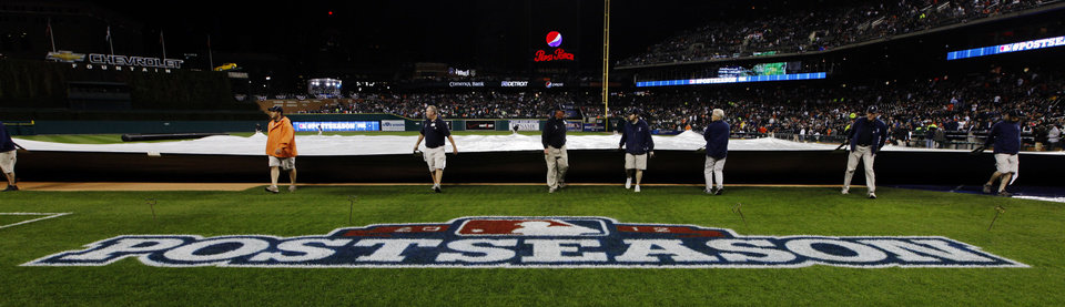 Photo -   Grounds crew members cover the field during a rain delay at Game 4 of the American League championship series between the Detroit Tigers and New York Yankees Wednesday, Oct. 17, 2012, in Detroit. (AP Photo/Paul Sancya )