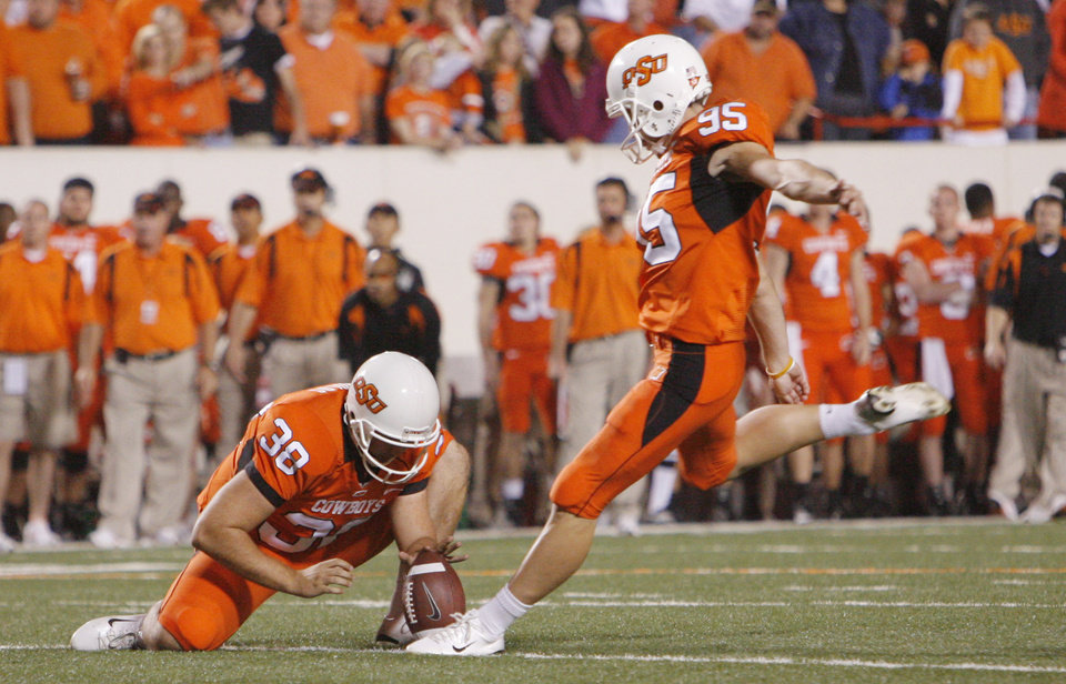 Photo - OSU kicker Dan Bailey (95) kicks as Josh Cooper (30) holds for a PAT at the college football game between Oklahoma State University (OSU) and Kansas University (KU) at Boone Pickens Stadium in Stillwater, Okla. Saturday, Nov. 10, 2007. BY NATE BILLINGS, THE OKLAHOMAN ORG XMIT: KOD