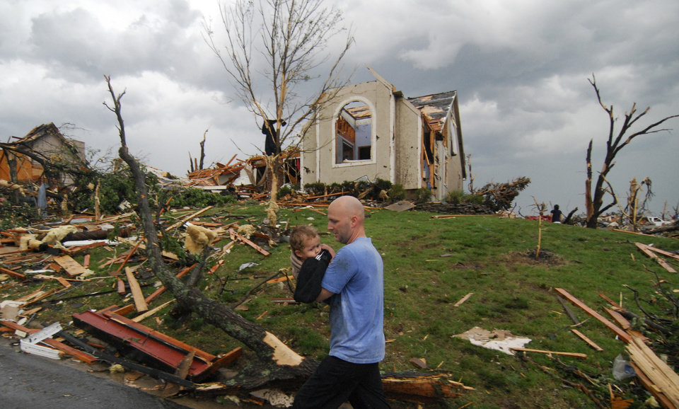 Photo - A man carries a young boy who was rescued after being trapped in his home after a tornado hit Joplin, Mo. on Sunday evening, May 22, 2011. The tornado tore a path a mile wide and four miles long destroying homes and businesses. (AP Photo/Mike Gullett) ORG XMIT: MOMG106