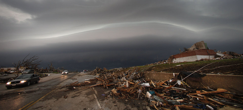 Photo - A shelf cloud containing a thunderstorm approaches a tornado-ravaged neighborhood in Joplin, Mo., Monday, May 23, 2011. A large tornado moved through much of the city Sunday, damaging a hospital, hundreds of homes and businesses and killing at least 89 people. (AP Photo/Charlie Riedel) ORG XMIT: MOCR202