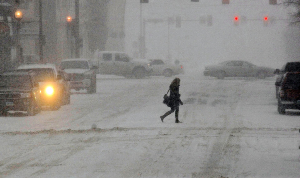 Photo - A pedestrian crosses the street in the snow, Monday, March 31, 2014, in Bismarck, N.D. Schools and universities across North Dakota are closing and no travel is advised in many areas because of a spring snow storm on Monday. (AP Photo/The Bismarck Tribune, Tom Stromme)