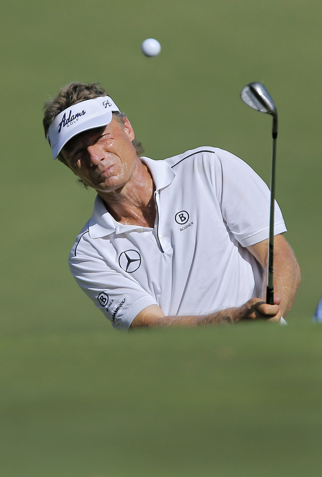 Photo - Bernhard Langer hits a shot during practice rounds for the U.S. Senior Open golf tournament at Oak Tree National in Edmond, Okla. on Tuesday, July 8, 2014. Photo by Chris Landsberger, The Oklahoman