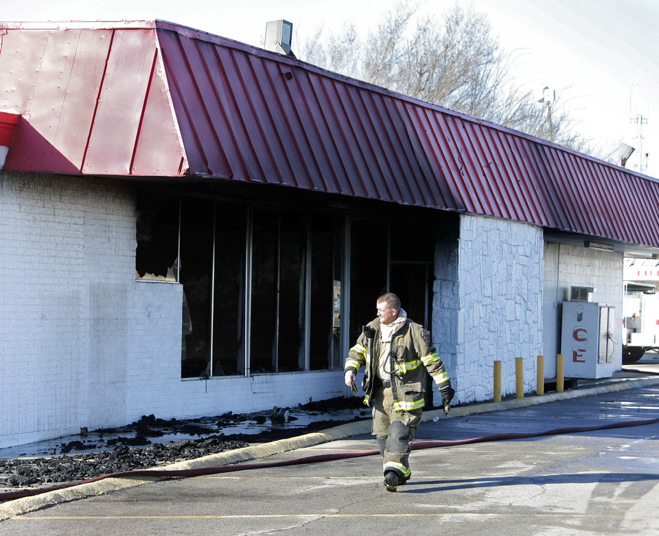 Below: A firefighter walks past the abandoned former grocery store in Tuttle that burned Thursday.