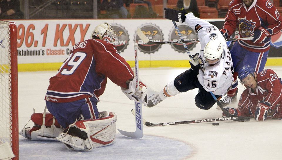 Oklahoma City's Magnus Paajarvi is tripped up by Hamilton's Brian Willsie as Hamilton's Peter Delmas defends the goal during the AHL hockey game between the Oklahoma City Barons and the Hamilton Bulldogs at the Cox Convention Center in Oklahoma City, Tuesday, April 3, 2012. Photo by Sarah Phipps, The Oklahoman