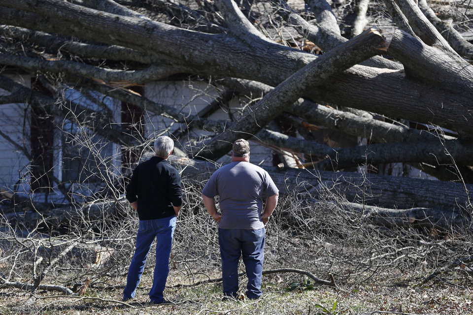 Photo - Two men stand next to a tree that covered damaged house , Wednesday, March 2, 2016, after a storm ripped through Bessemer, Ala., on Tuesday evening. Forecasters say a tornado that severely damaged homes and trees in the Birmingham suburb has been determined as an EF2, with winds of between 120 and 125 mph.  (AP Photo/Brynn Anderson)