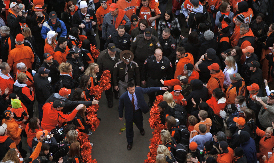 Photo - Oklahoma State coach Mike Gundy walks through fans during the Spirit Walk before the Bedlam college football game between the Oklahoma State University Cowboys (OSU) and the University of Oklahoma Sooners (OU) at Boone Pickens Stadium in Stillwater, Okla., Saturday, Dec. 3, 2011. Photo by Bryan Terry, The Oklahoman