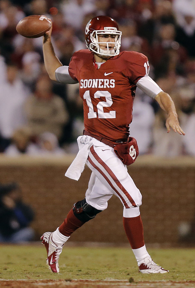 Photo - OU's Landry Jones (12) passes the ball on the run during the college football game between the University of Oklahoma Sooners (OU) and the Notre Dame Fighting Irish at the Gaylord Family-Oklahoma Memorial Stadium on Saturday, Oct. 27, 2012, in Norman, Okla. Photo by Chris Landsberger, The Oklahoman