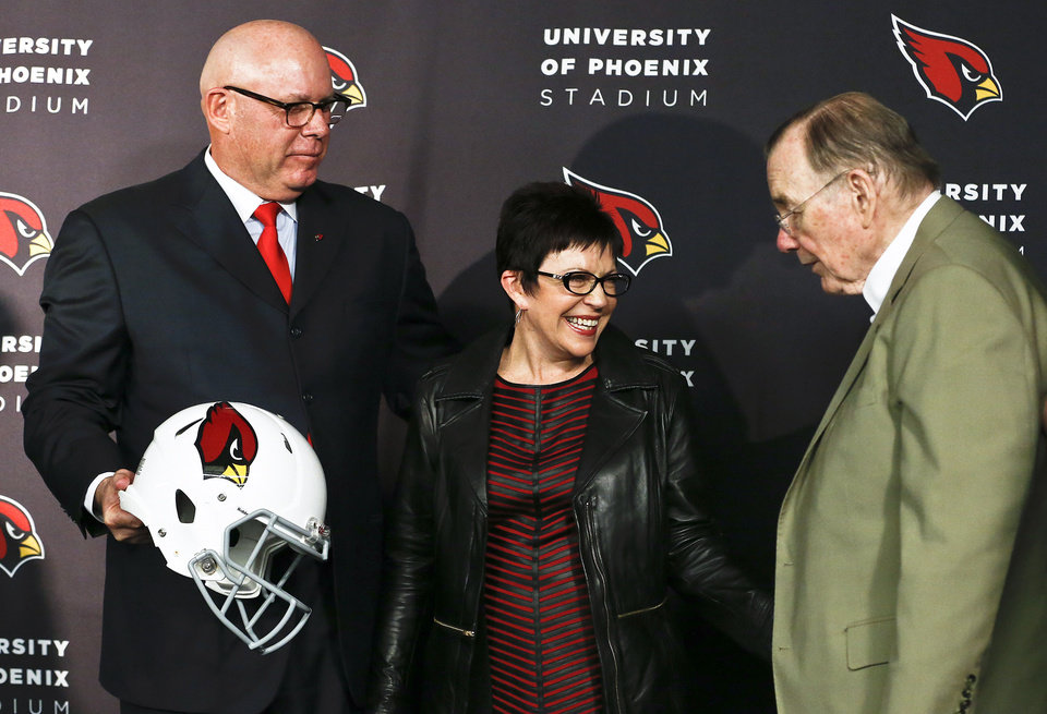 Photo - Arizona Cardinals owner William Bidwill, right, talks with new head coach Bruce Arians, left, and his wife Christine Arians after Arians was introduced during an NFL football news conference at the team's training facility Friday, Jan. 18, 2013, in Tempe, Ariz.  The Cardinals bring in Arians after he had a storybook year as the Indianapolis Colts offensive coordinator-turned-temporary coach. He filled in for head coach Chuck Pagano while he was treated for cancer and helped get the Colts to the NFL playoffs.(AP Photo/Ross D. Franklin)