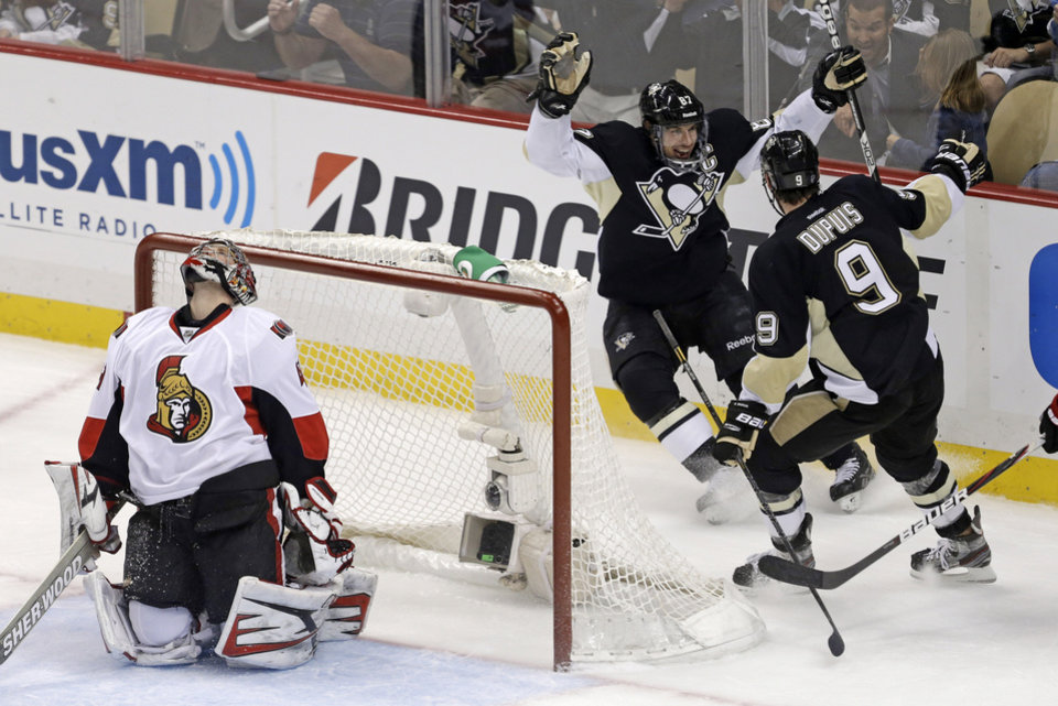 Photo - Pittsburgh Penguins' Sidney Crosby (87) celebrates with teammate Pascal Dupuis (9) as Ottawa Senators goalie Craig Anderson (41) reacts to Crosby's second goal of the first period of Game 2 of an NHL hockey Stanley Cup second-round playoff series, in Pittsburgh on Friday, May 17, 2013. (AP Photo/Gene J. Puskar)