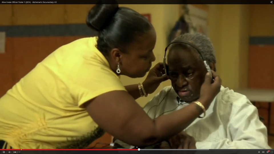 "Photo - Yvonne Russell, recreation therapist at Cobble Hill Health Center in Brooklyn, New York, places headphones on Henry Dryer, a patient with severe memory loss.  Image from ""Alive Inside."""