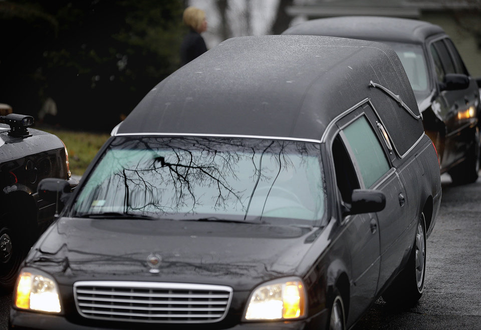 Photo - A hearse leads the funeral procession to the cemetery for Sandy Hook Elementary School shooting victim, Jack Pinto, 6, Monday, Dec. 17, 2012, in Newtown, Conn. Pinto was killed when a gunman walked into Sandy Hook Elementary School in Newtown Friday and opened fire, killing 26 people, including 20 children.(AP Photo/David Goldman) ORG XMIT: CTDG121