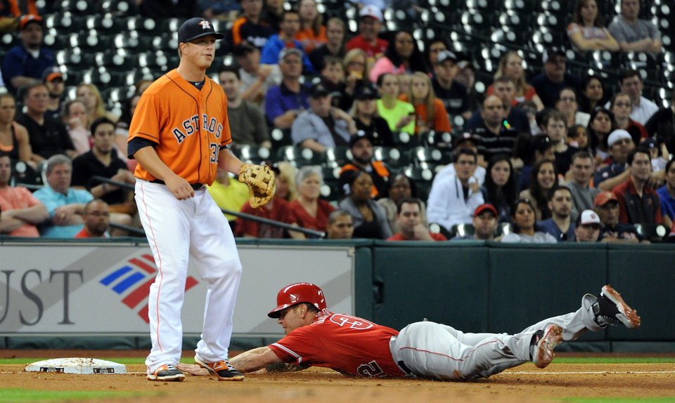 Photo - Los Angeles Angles' Josh Hamilton, right, slides into third base past Houston Astros' Matt Dominguez after a David Freese single in the third inning of a baseball game on Friday, April 4, 2014, at Minute Maid Park in Houston. (AP Photo/Eric Christian Smith)