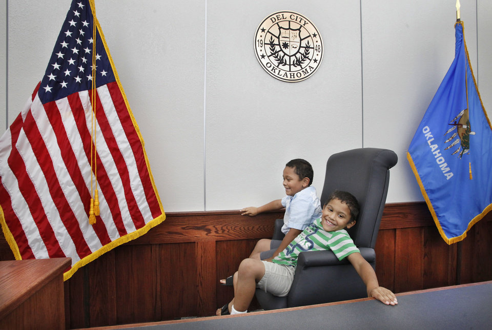 Photo - Brothers Nicholas Butler, 5, and Edwin Butler, Jr., 6, swivel in the judge's chair as they sit at the bench in the Del City municipal courtroom. They were taking the open house tour. The new police station in Del City was officially dedicated Thursday afternoon.  Jim Beckel - THE OKLAHOMAN
