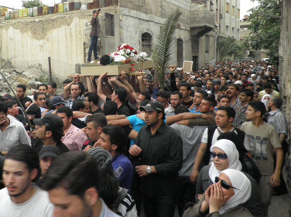 Photo -   Anti-Syrian regime mourners shout slogans and carry the body of activist Nour al-Zahraa, 23, who was shot by Syrian security forces on Sunday, during his funeral procession, in the Kfar Suseh area, in Damascus, Syria, on Monday, April 30, 2012. (AP Photo)