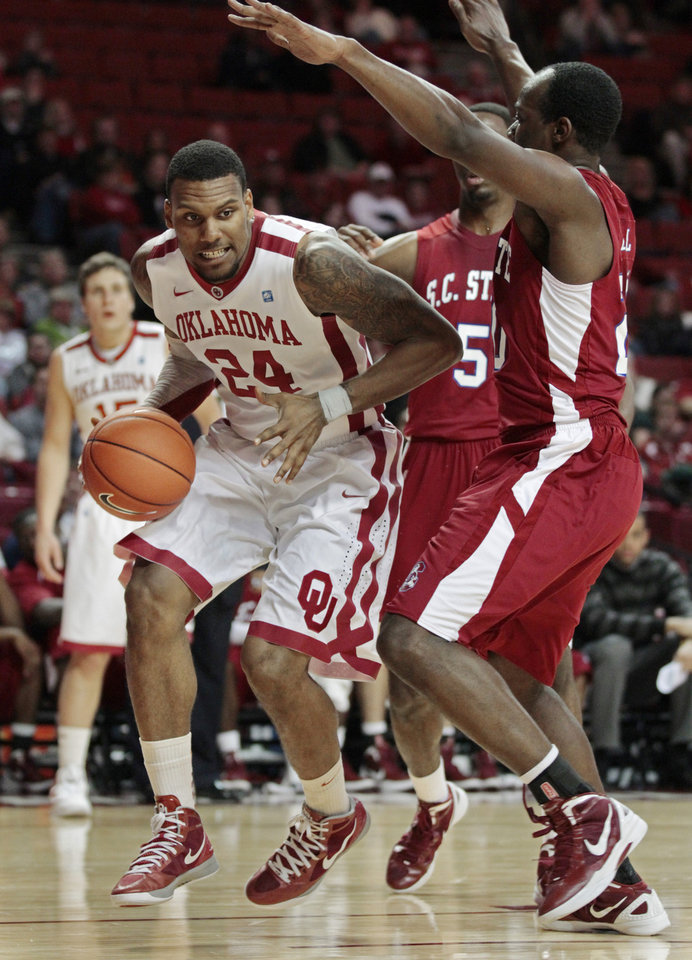 Photo - Oklahoma Sooners' Romero Osby (24) looks for a shot as he drives past South Carolina State Bulldogs' Presano Bell (20) and South Carolina State Bulldogs' Omar Sanders (5) as the University of Oklahoma (OU) Sooners play the South Carolina State Bulldogs in men's college basketball at the Lloyd Noble Center on Wednesday, Dec. 21, 2011, in Norman, Okla.  Photo by Steve Sisney, The Oklahoman