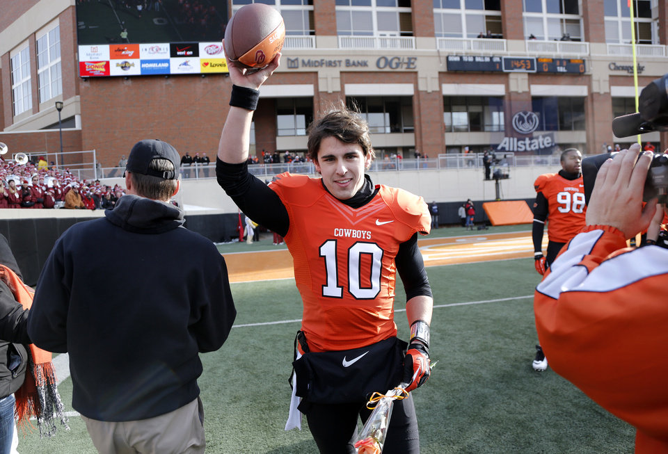 Photo - Oklahoma State's Clint Chelf (10) waves to the fans after being honored on senior day during the Bedlam college football game between the Oklahoma State University Cowboys (OSU) and the University of Oklahoma Sooners (OU) at Boone Pickens Stadium in Stillwater, Okla., Saturday, Dec. 7, 2013. Photo by Chris Landsberger, The Oklahoman
