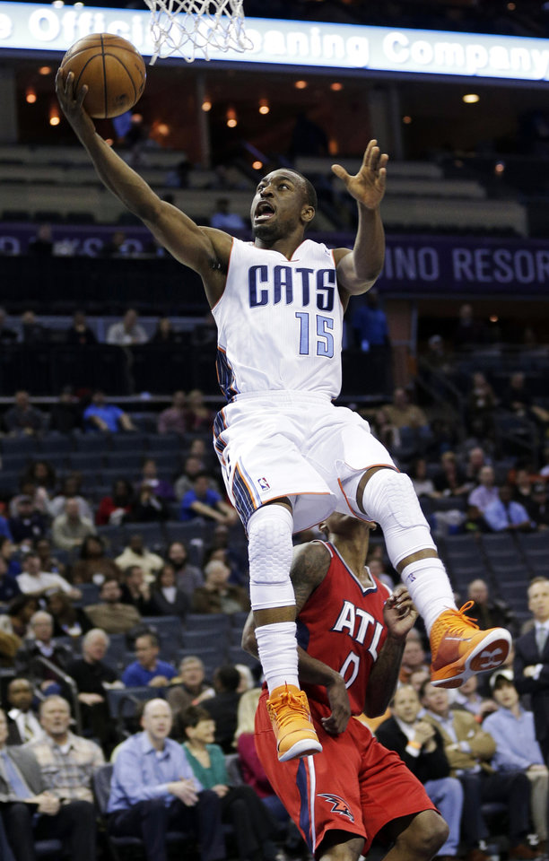 Photo - Charlotte Bobcats' Kemba Walker (15) drives past Atlanta Hawks' Jeff Teague (0) during the first half of an NBA basketball game in Charlotte, N.C., Wednesday, Jan. 23, 2013. (AP Photo/Chuck Burton)