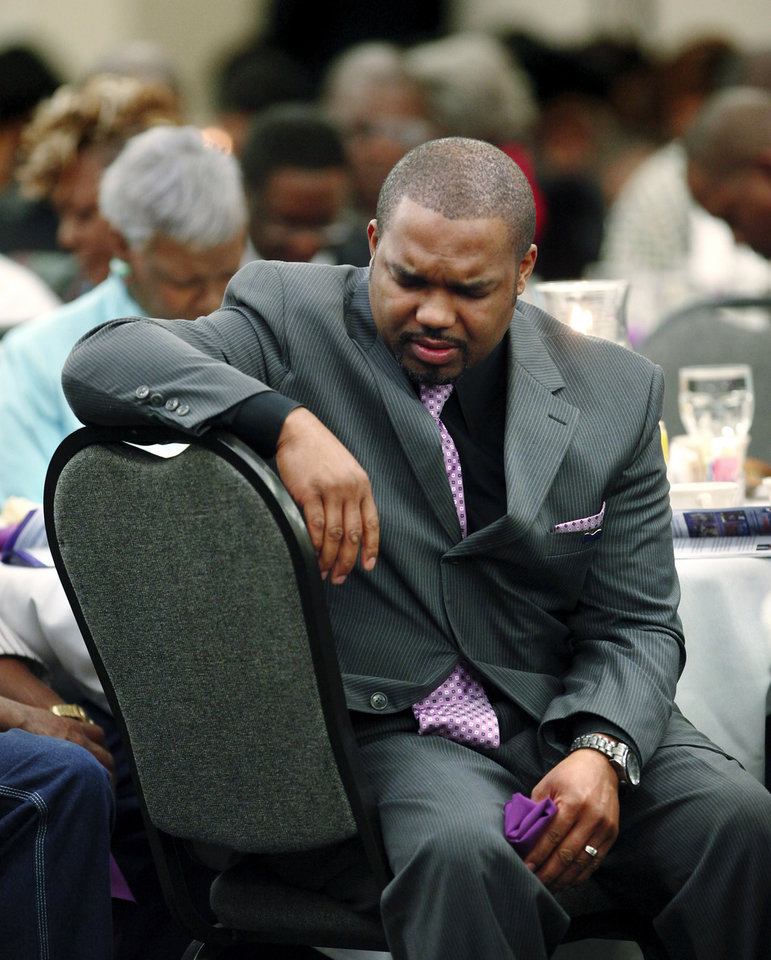 Photo - A man prays at his seat during the 16th annual Midwest City Dr. Martin Luther King, Jr. Prayer Breakfast inside the Reed Conference Center Monday morning, Jan. 21, 2013. The theme of this year's event is
