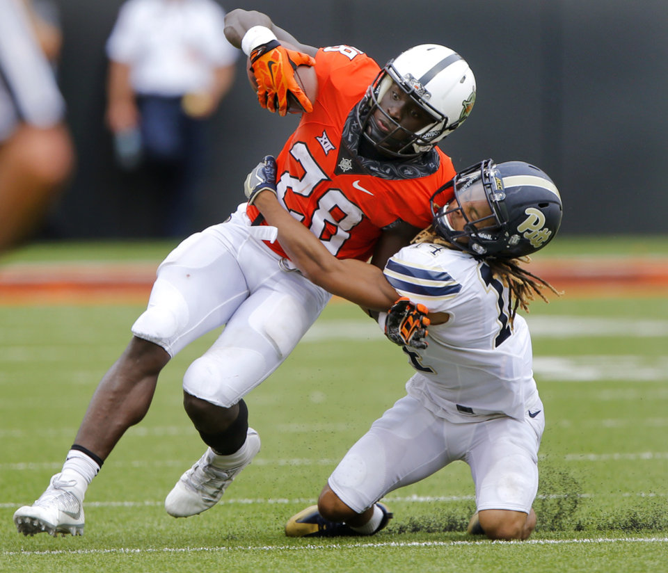 Photo - Pittsburgh's Avonte Maddox (14) tries to bring down Oklahoma State's James Washington (28) during a college football game between the Oklahoma State Cowboys (OSU) and the Pitt Panthers at Boone Pickens Stadium in Stillwater, Okla., Saturday, Sept. 17, 2016. Photo by Chris Landsberger, The Oklahoman